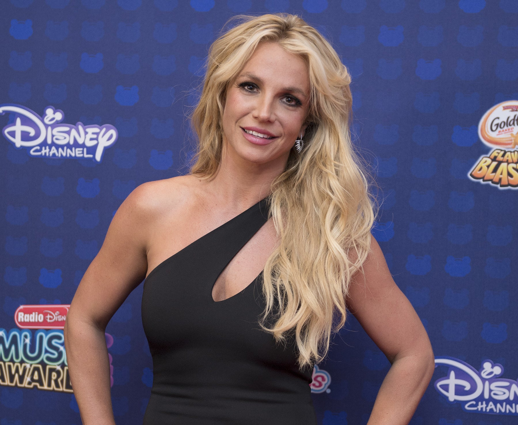 Britney wears a one-shoulder black dress while posing with her hands on her hips