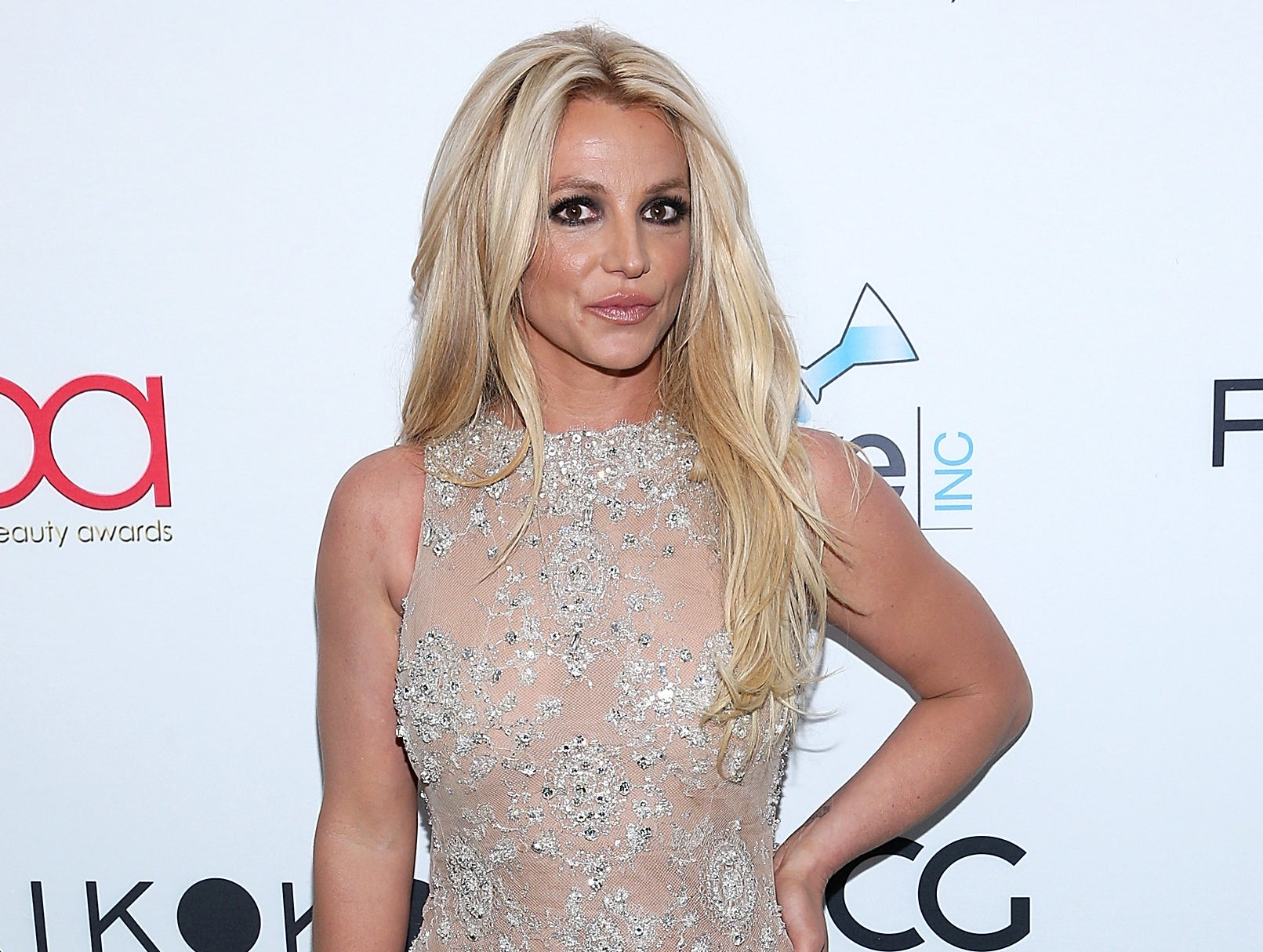 Britney wears a nude sleeveless dress with crystal detailing