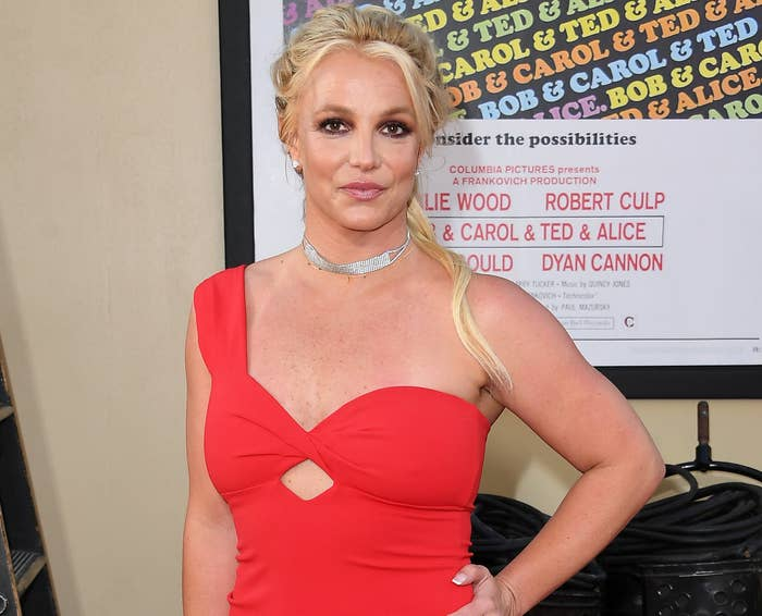 Britney wears a one-shoulder red dress while at an event