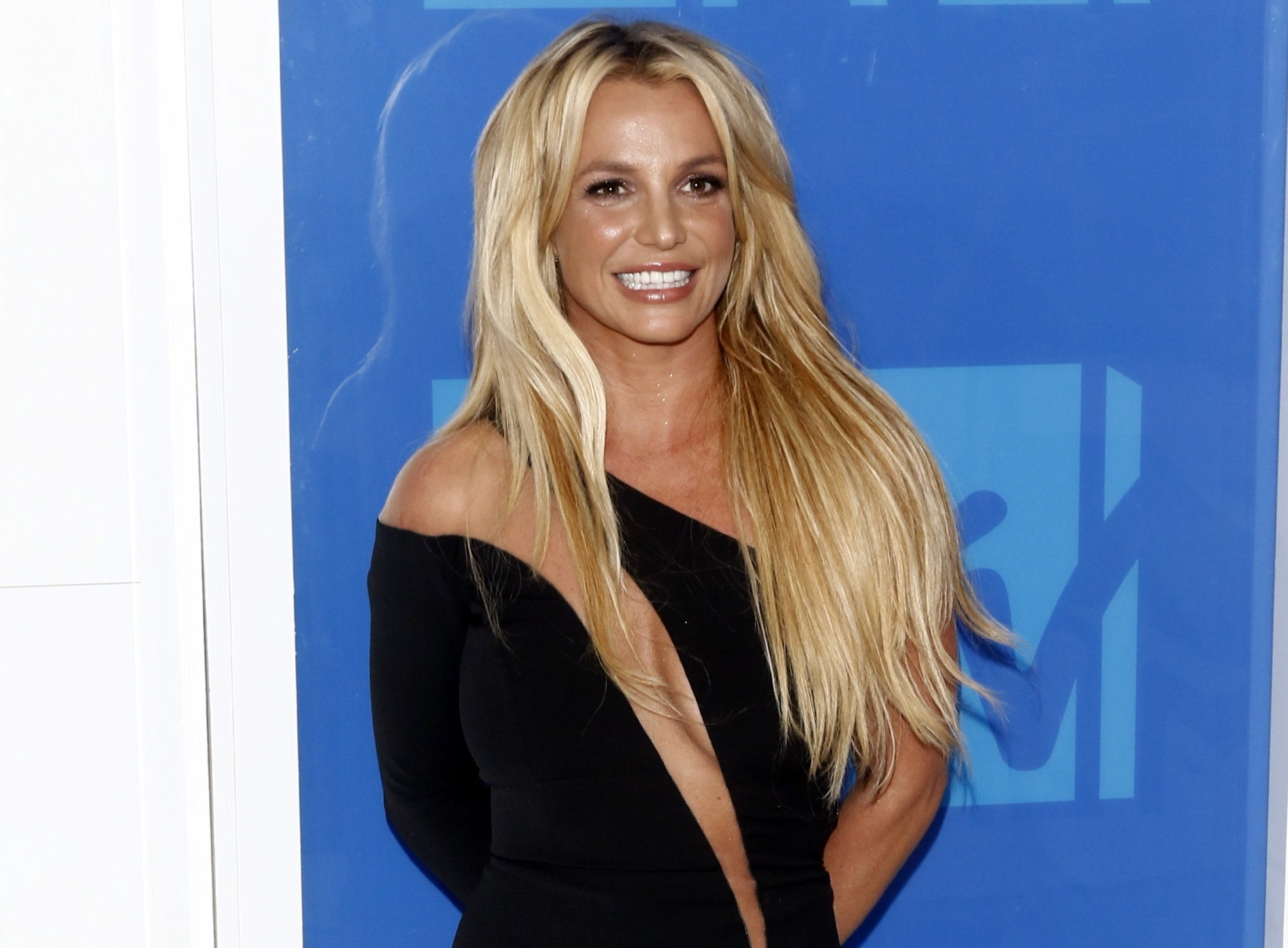 Britney smiles in a one-shoulder dress with a long sleeve and a cutout down the center