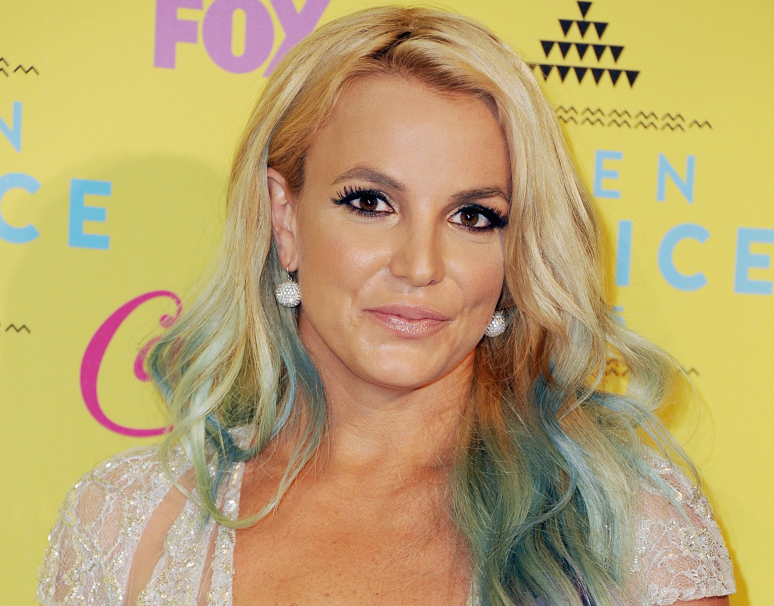Britney smiles softly while showing off blue streaks in her hair