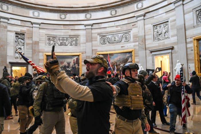Several people wearing military-style fatigues and holding US flags are packed into the Capitol rotunda