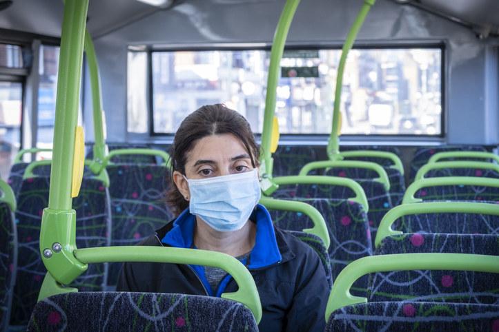 A woman sitting alone on a public bus