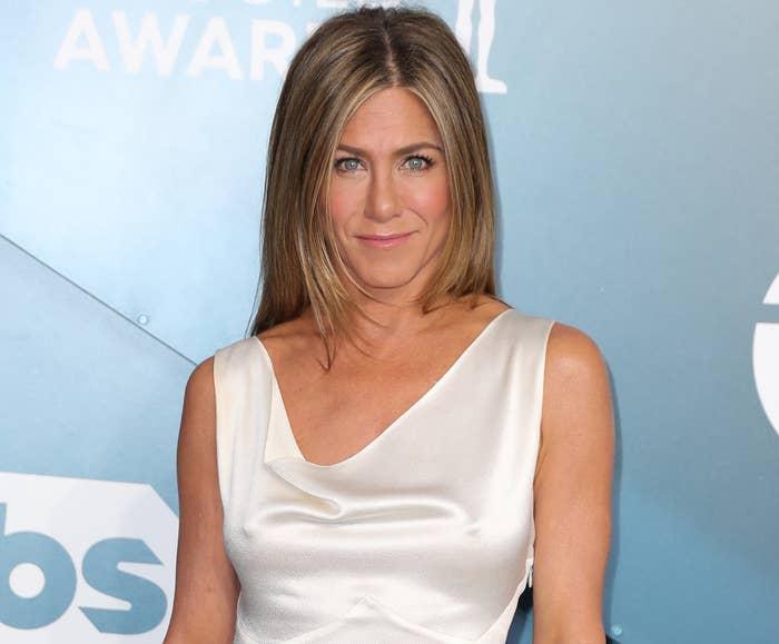 Jennifer wears a white dress with a cowl neckline