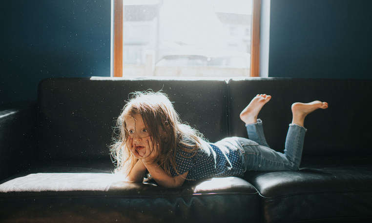 A little girl sitting alone on a couch