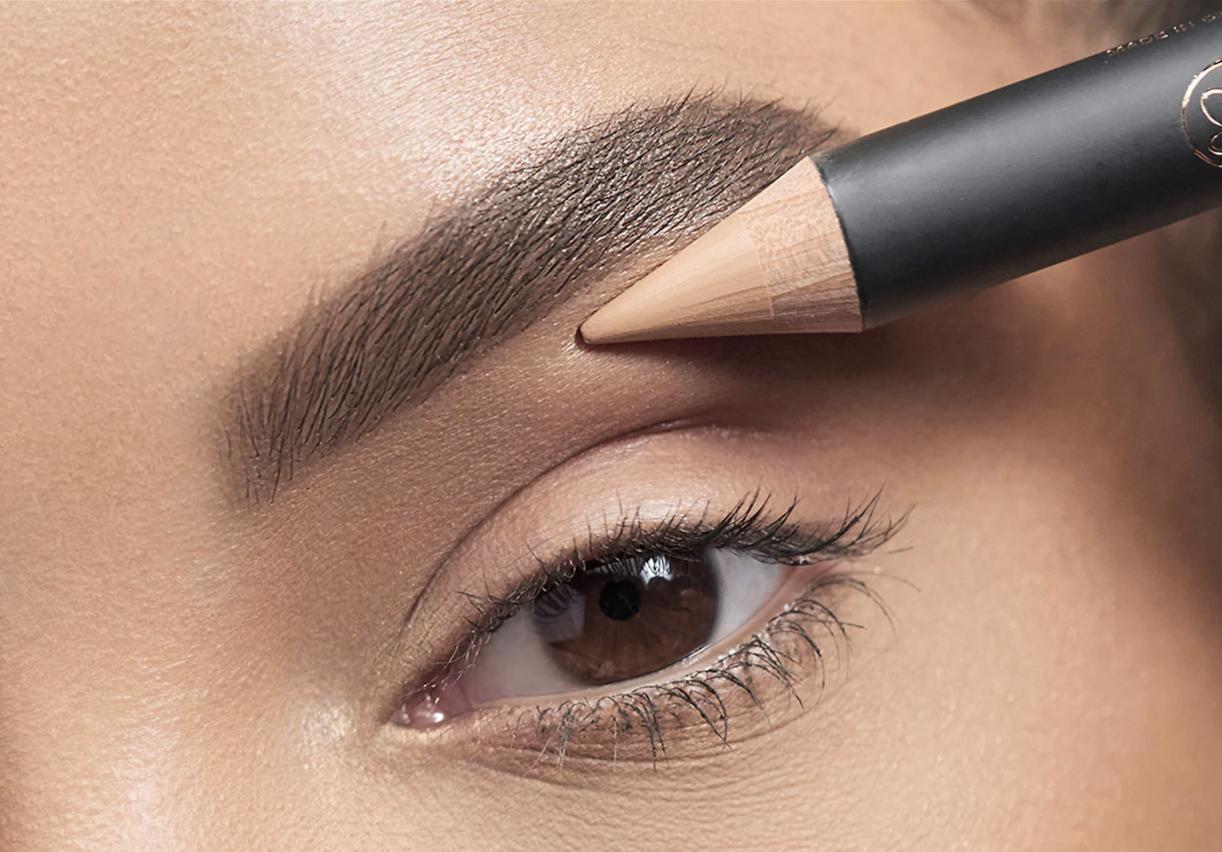 model applying the crayon to their brow bone