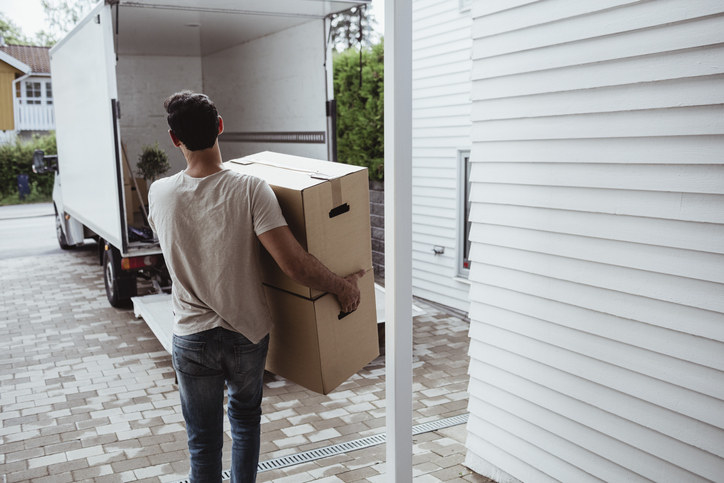A man carrying moving boxes into a moving truck