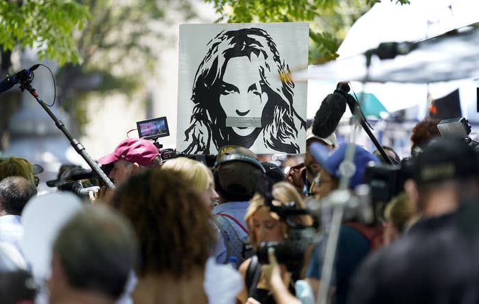 In a crowd, someone holds up a sign that depicts Britney Spears' face with duct tape covering her mouth