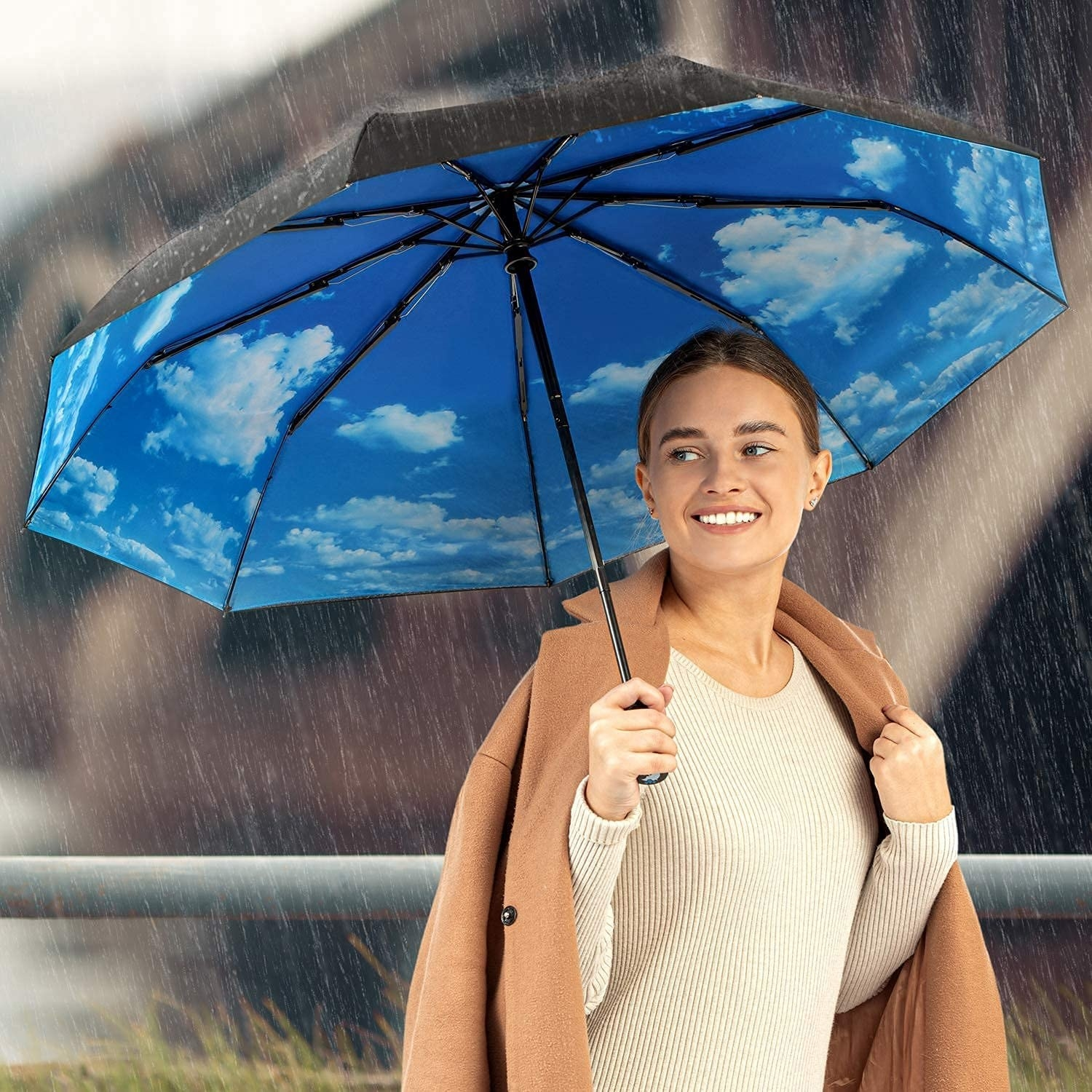 A smiling person holding an umbrella; a cloud graphic is visible on the underside of the canopy