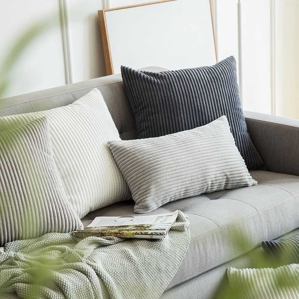 Several pillows in corduroy covers on a couch