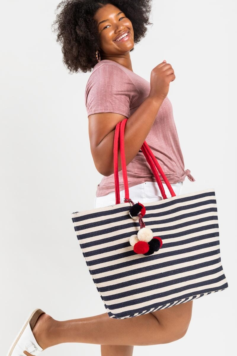 model holding a navy blue and white striped tote with red handles and pom poms