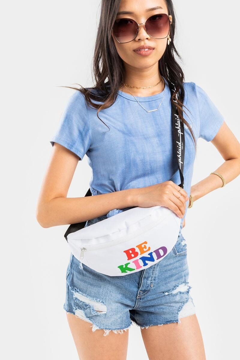 """model carrying a white fanny pack with colorful """"be kind"""" on the front"""