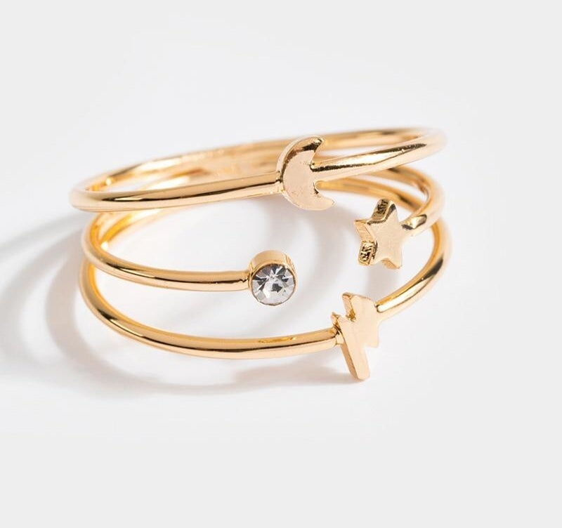 gold colored ring with moon, stars, and crystal