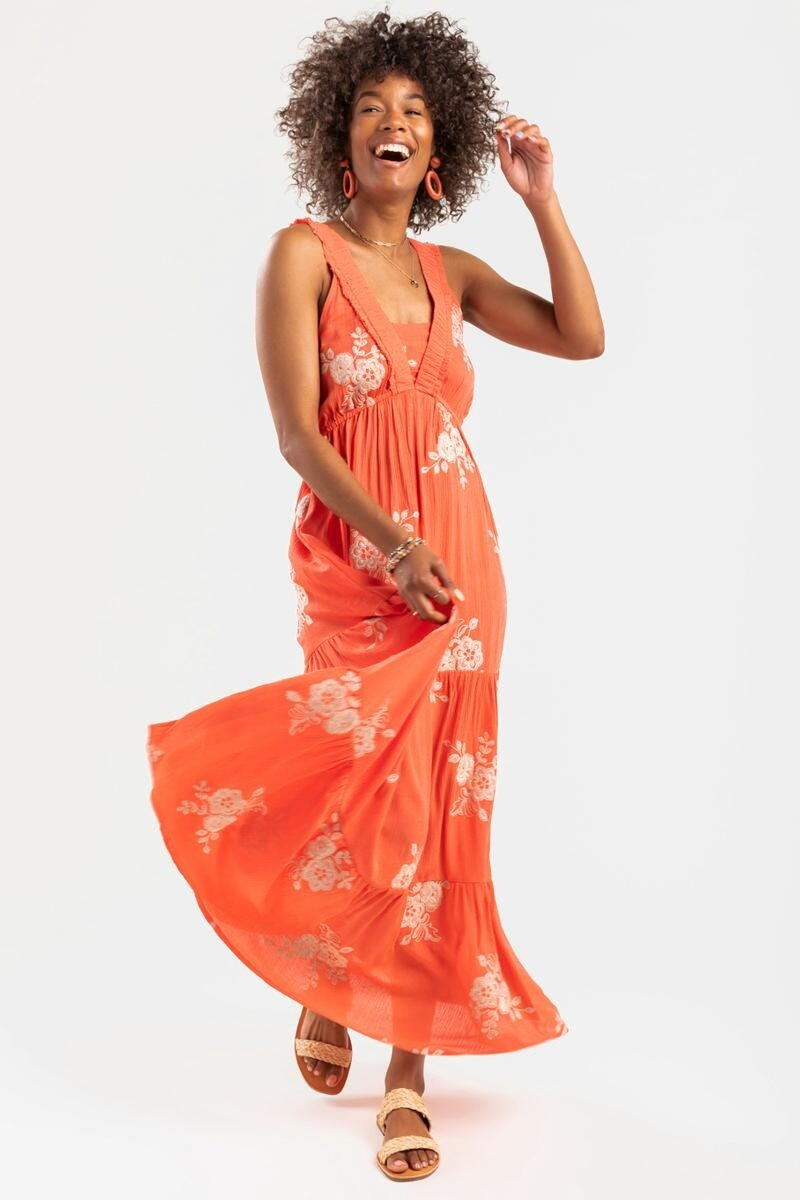 model wearing an orange floral maxi dress