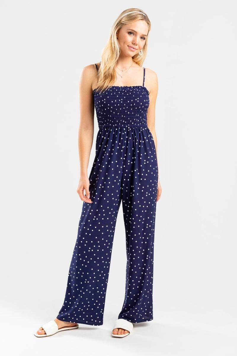 model wearing a long blue and white polka dot jumpsuit with adjustable straps