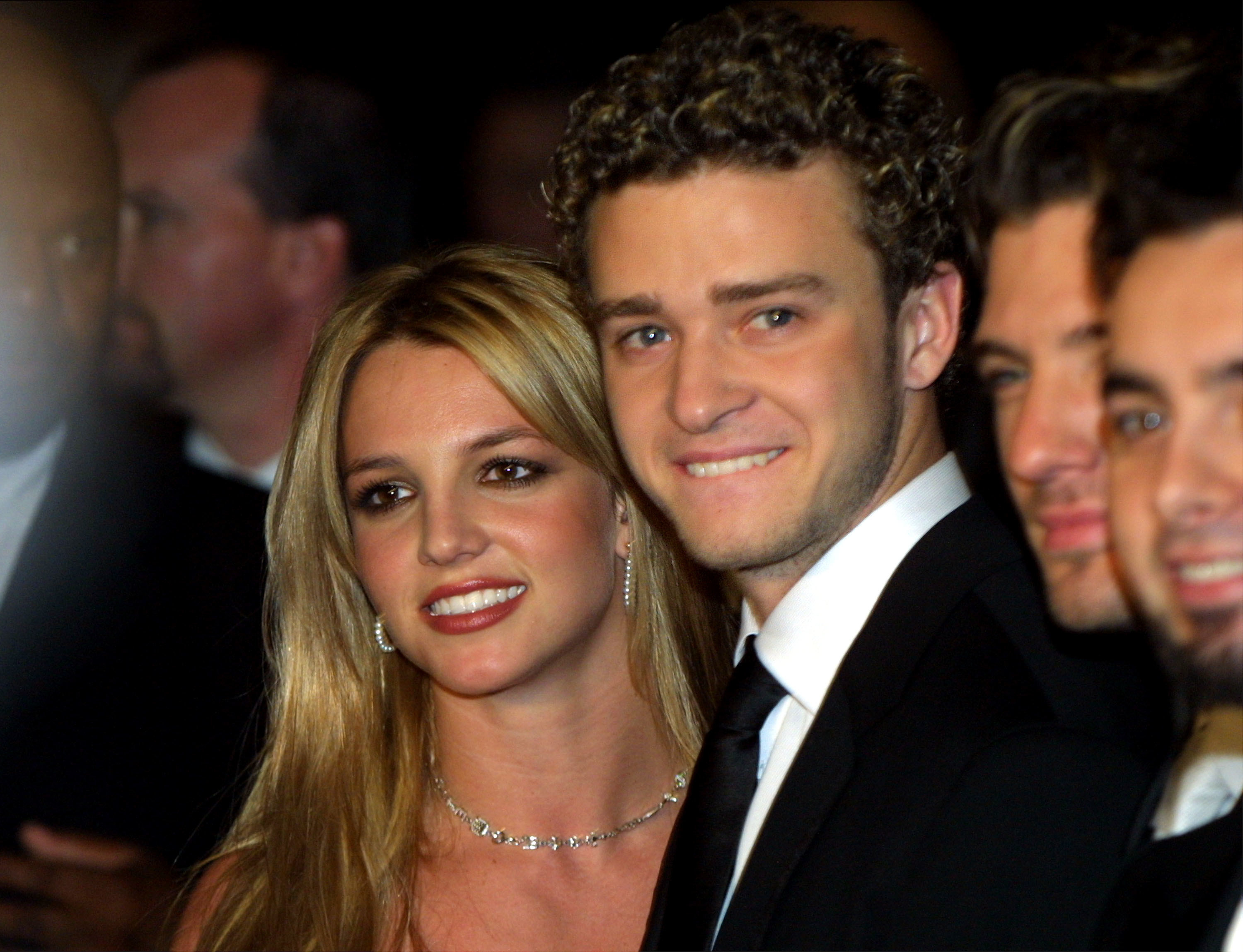 Spears stands next to Timberlake while both of them smile