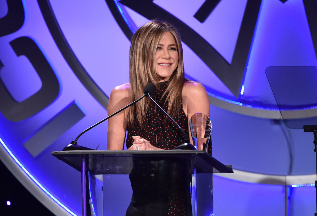 Jennifer Aniston smiles on stage while making speech.