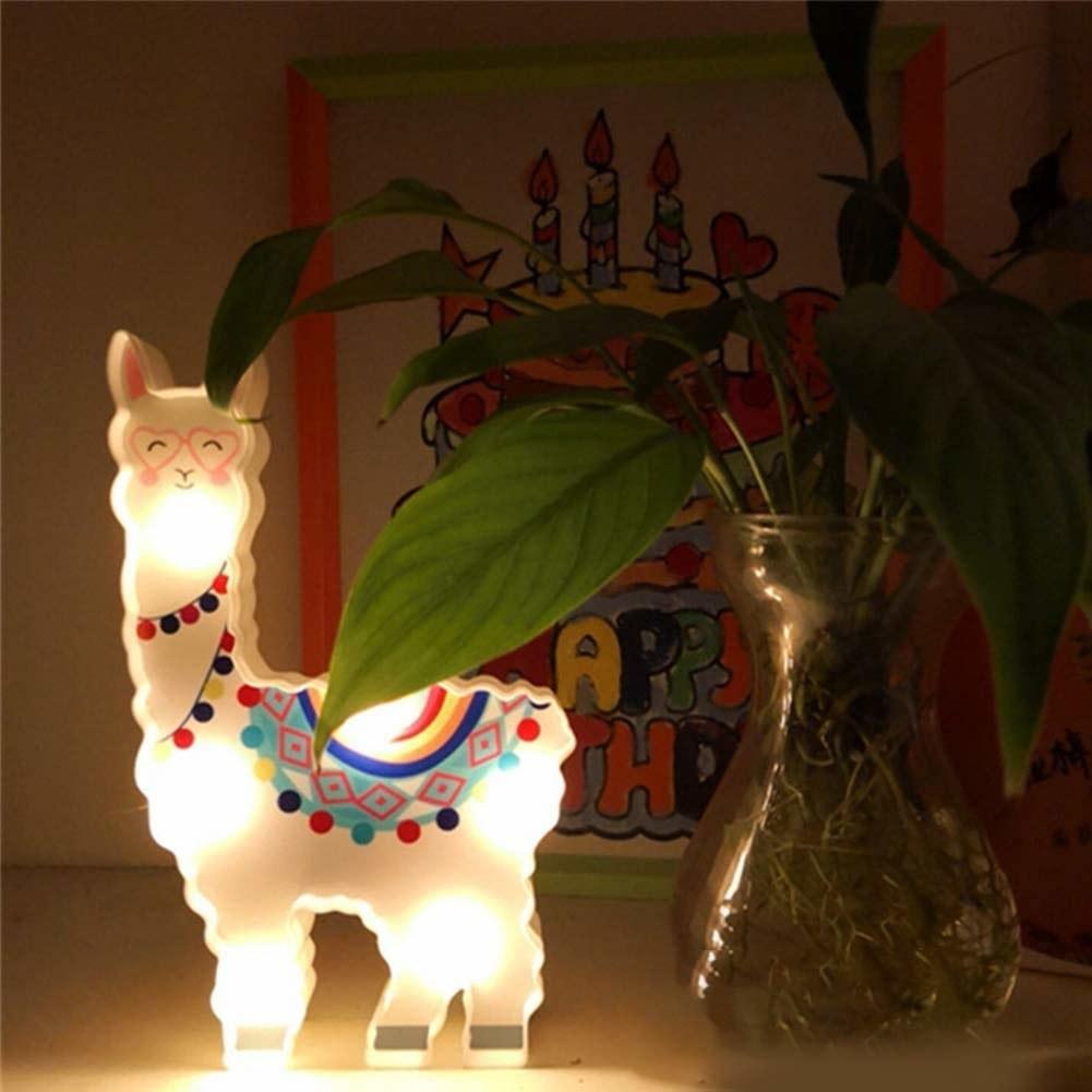 A llama lamp on a table beside a pot of plants