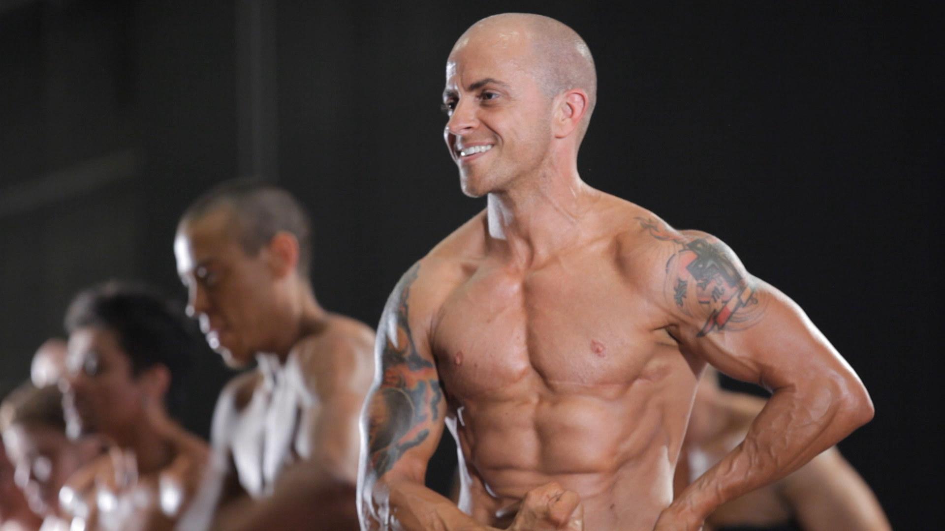 A trans bodybuilder strikes a pose
