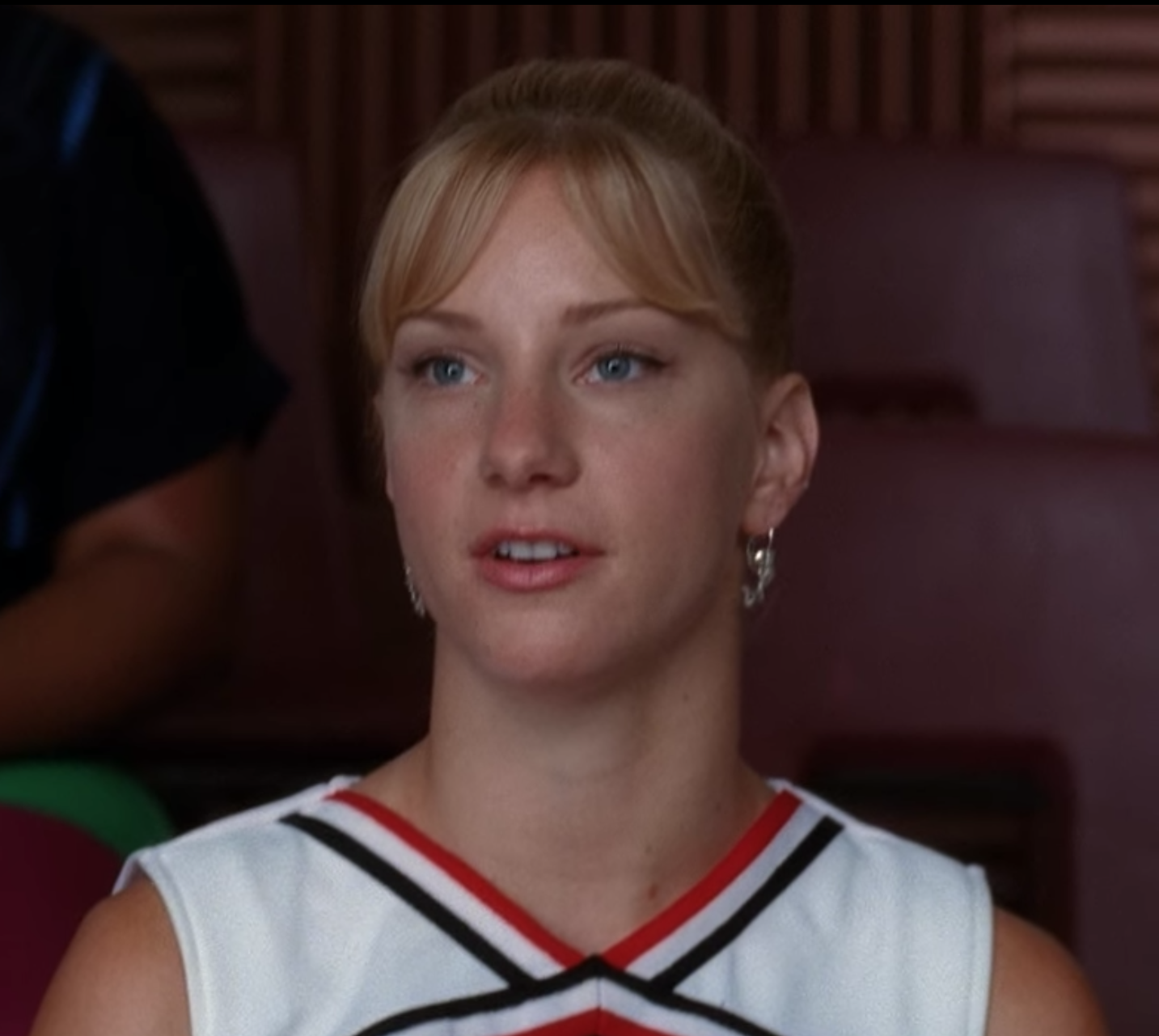 A close up of Brittany S. Pierce as she wears her red, black, and white striped cheerleading uniform top.