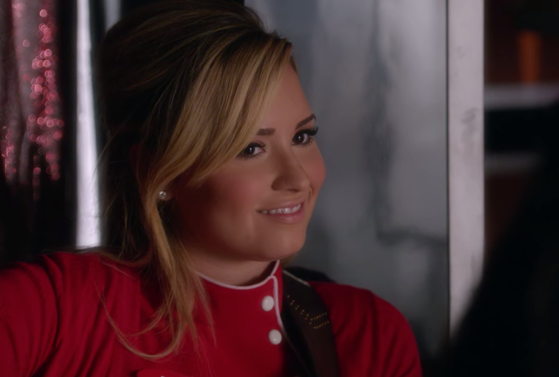 Dani, wearing her red and white waitress uniform, smiles softly at Santana Lopez.