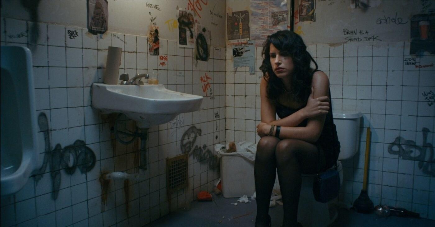 Desiree Akhavan sits on a toilet