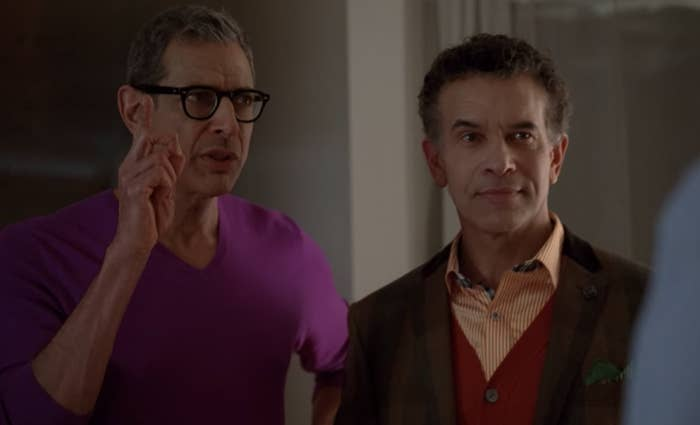 Hiram Berry wears a purple v-neck shirt with his index finger pointed in the air and Leroy Berry wears a red vest over a orange and white striped shirt under a brown blazer.