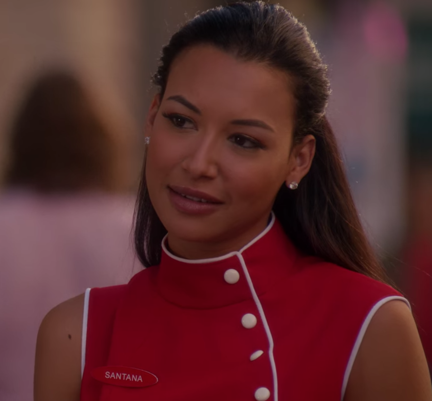 Santana Lopez stands on a street in NYC wearing her red turtleneck sleeveless waitress uniform.