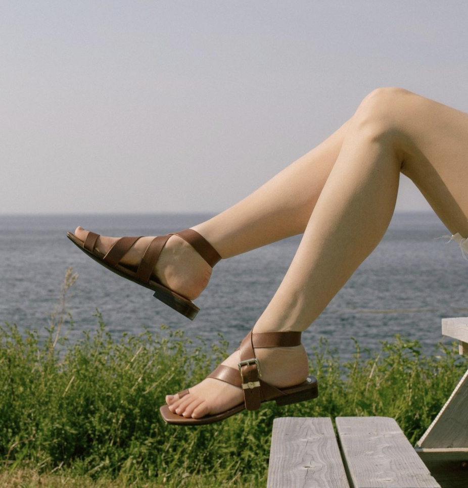 person's feet with the shoes on sitting on a picnic table