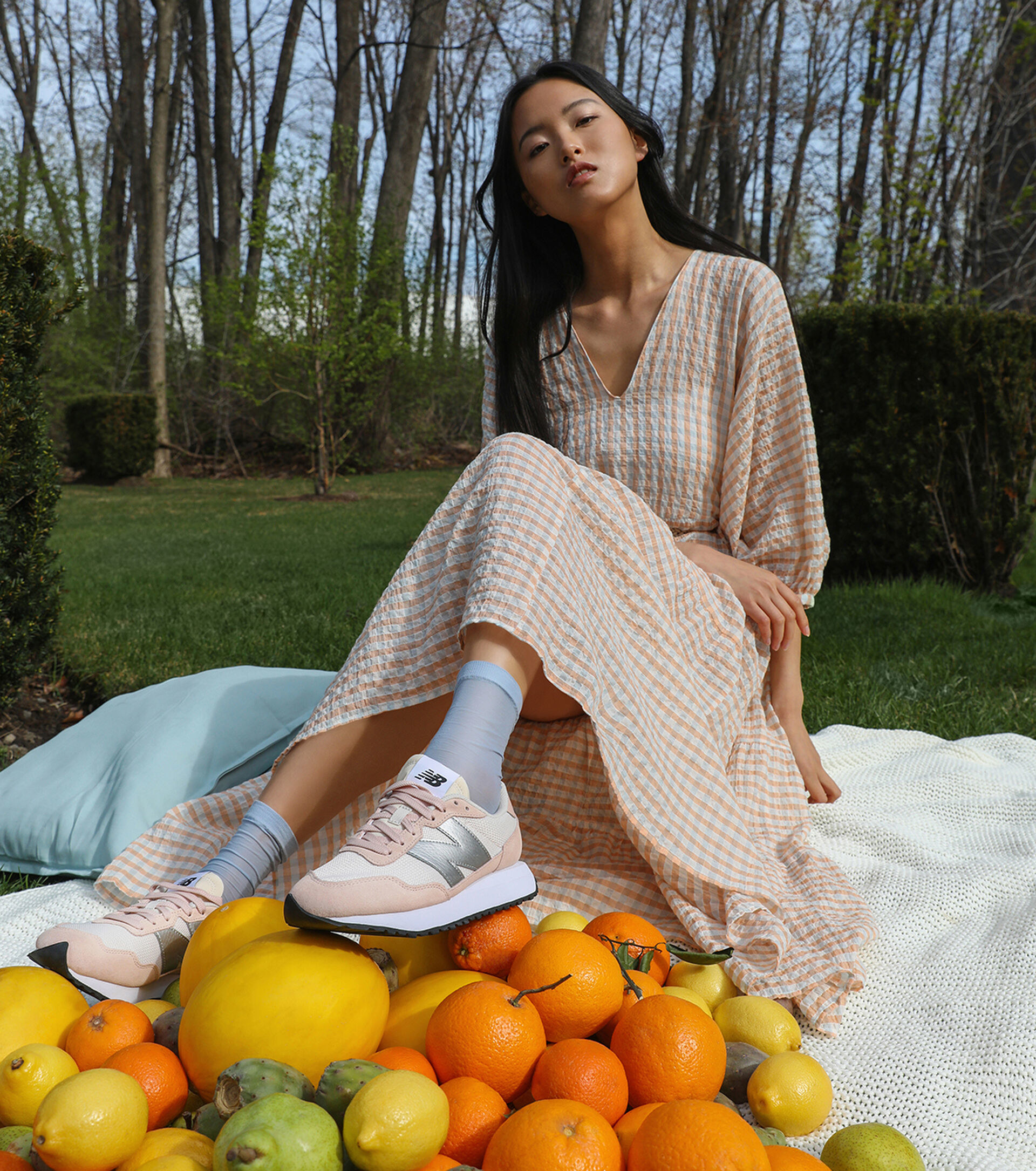 person sitting in a park with the shoes on an a pile of citrus