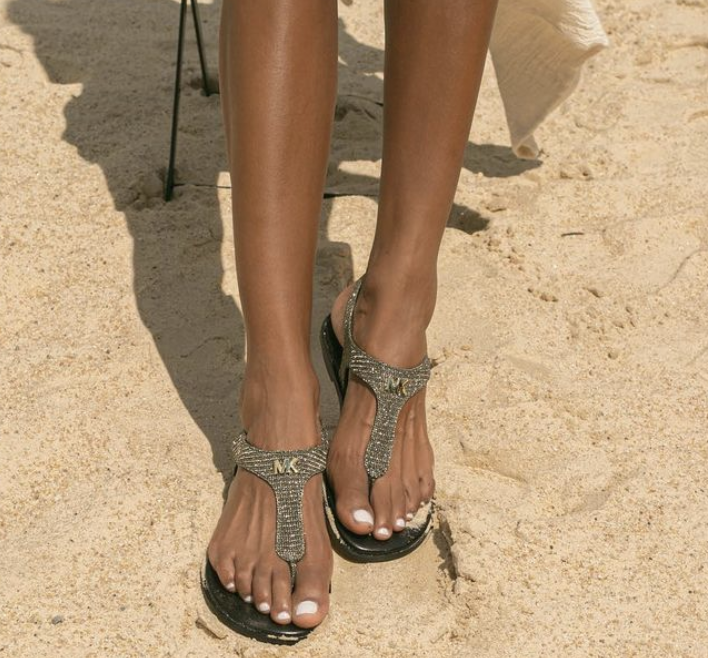 person wearing the shoes in the sand