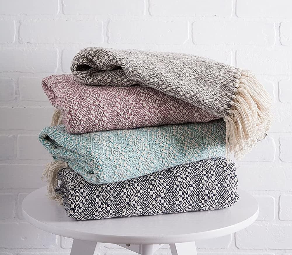 four throw blankets on a table
