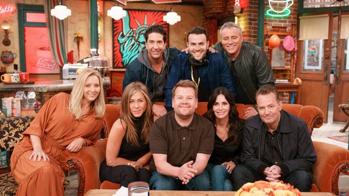 Lisa Kudrow, Jennifer Aniston, Courteney Cox, David Schwimmer, Matt LeBlanc, Matthew Perry, and James Corden smile while sitting on a couch