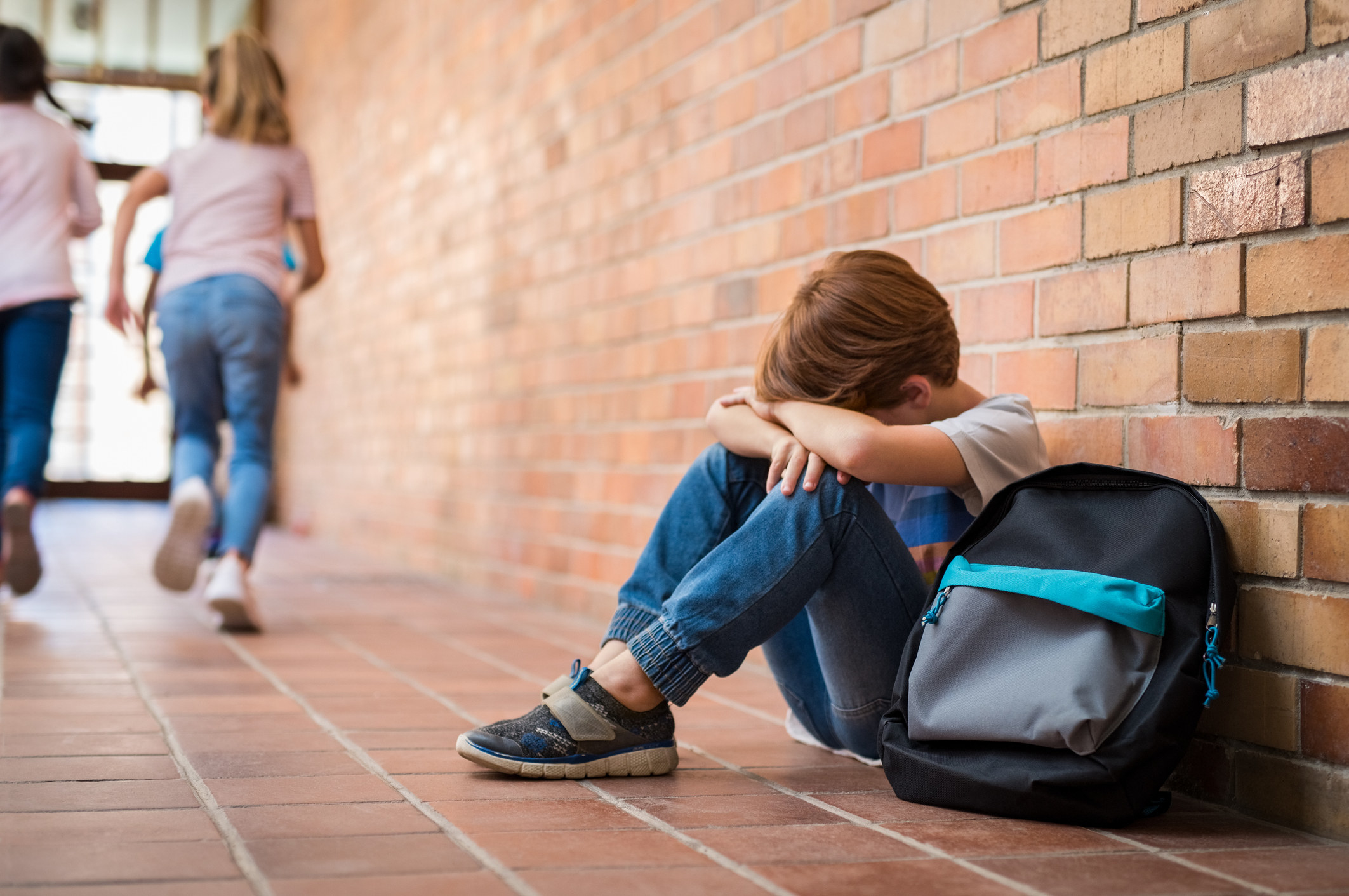 Young boy sitting alone outside in a hallway while two young girls run in the background