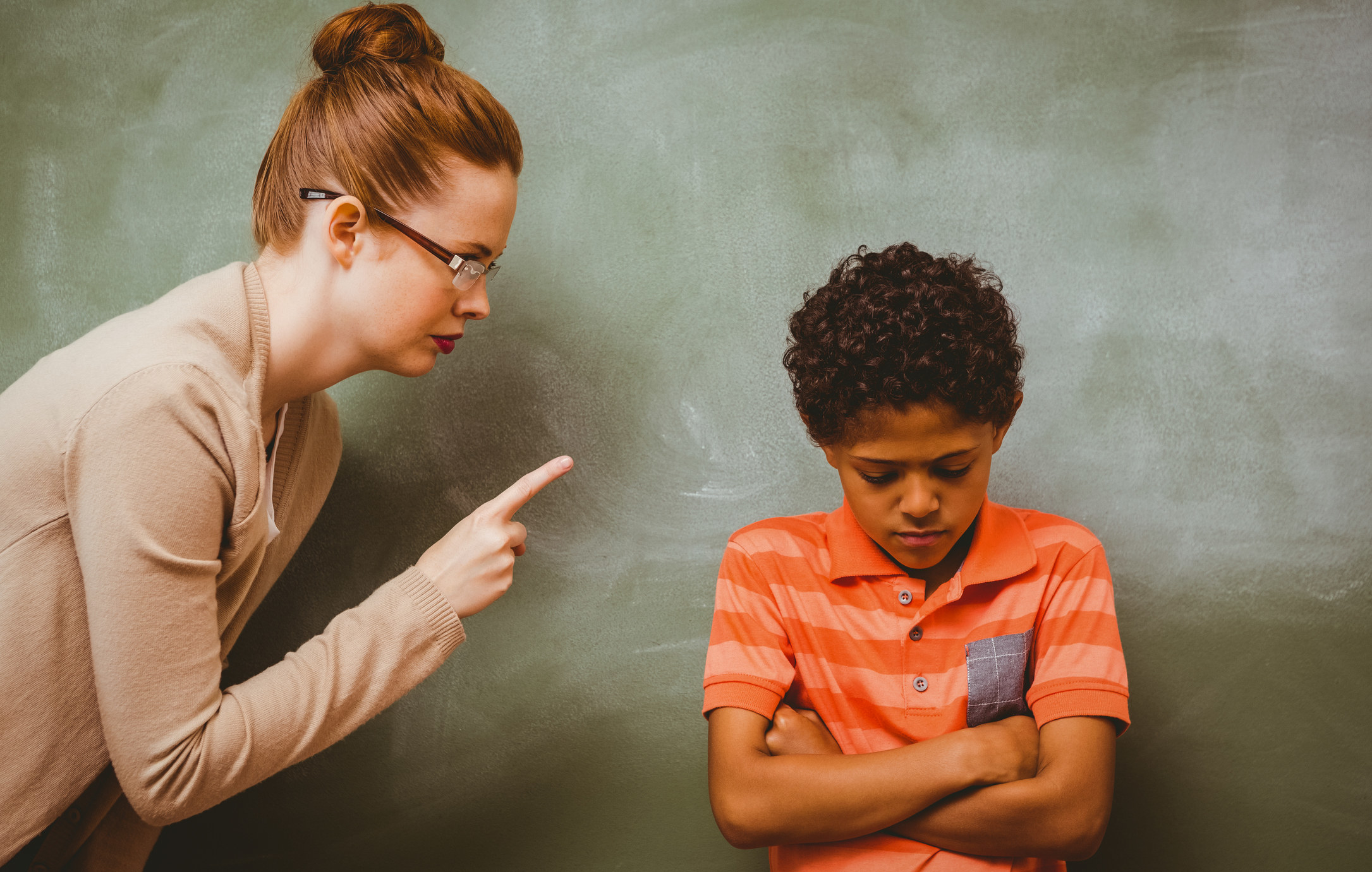 Female teacher shouting at boy in the classroom