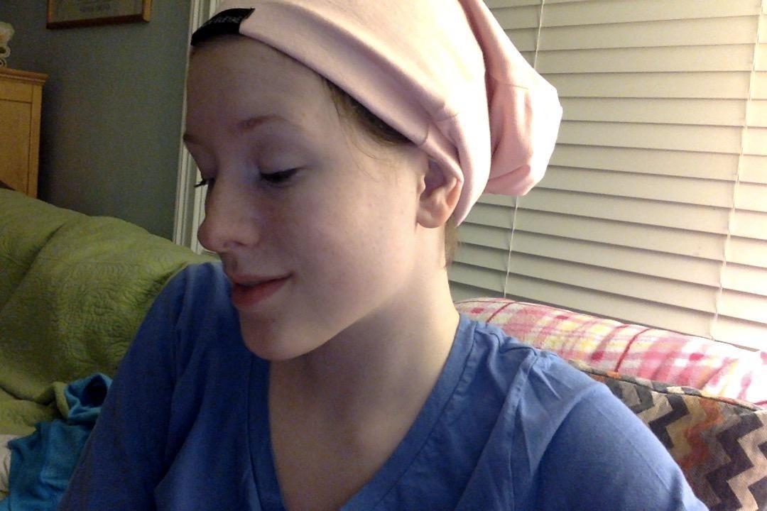 Reviewer wearing pink satin cap