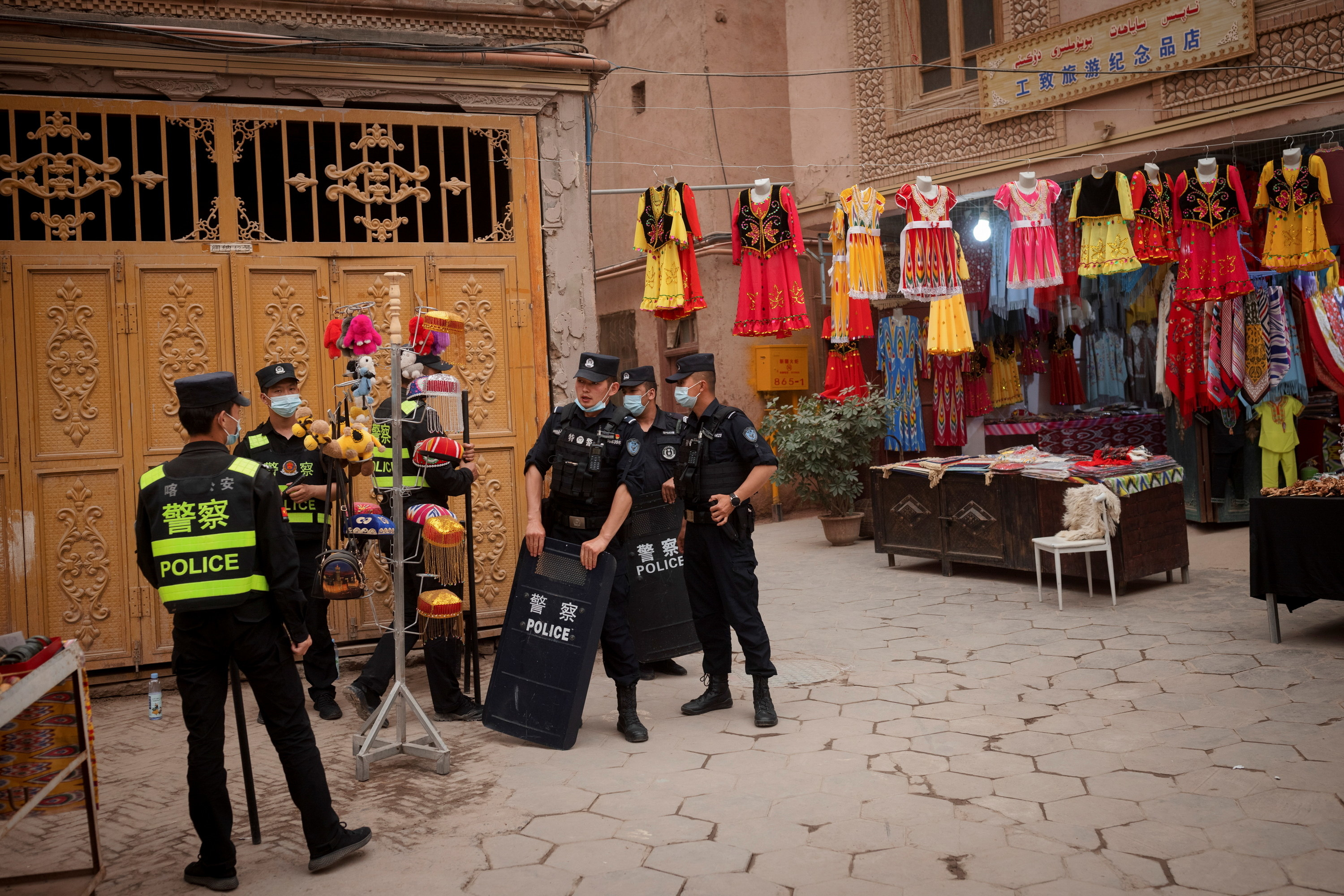 A group of Chinese polica officers outside a tourist stand selling dresses and hates in Xinjiang
