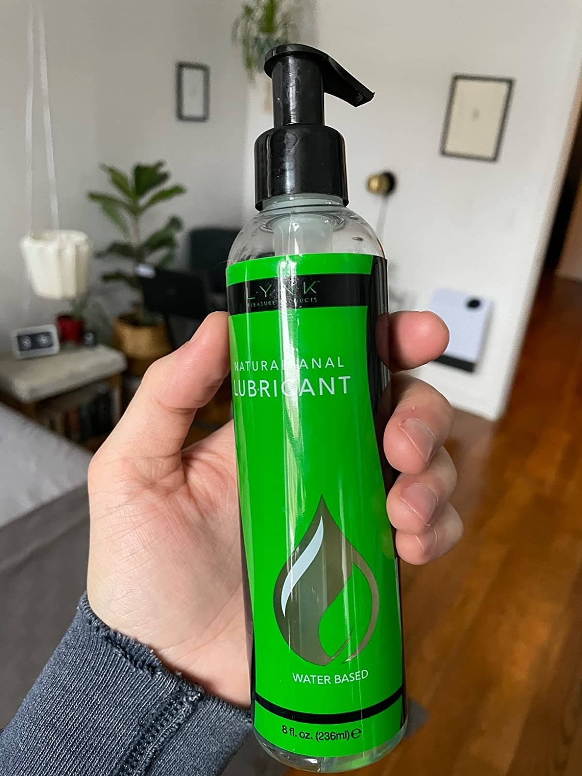 Model holding green bottle of Lynk personal lubricant