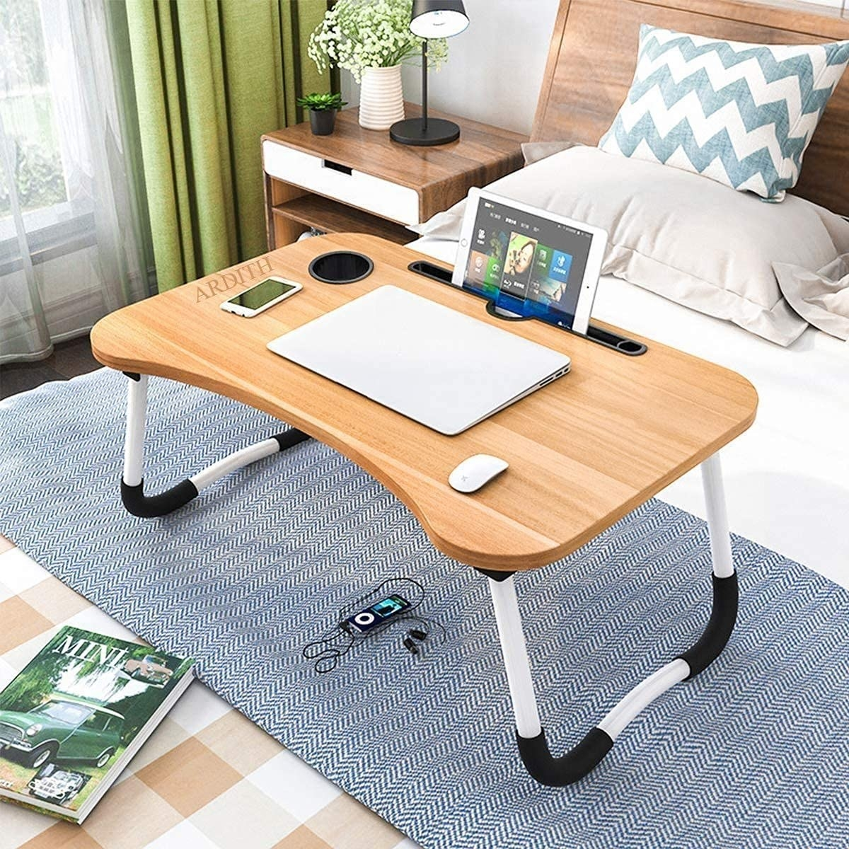 Foldable portable table kept on a bed. There's a laptop, tablet, mouse, and phone kept on it.