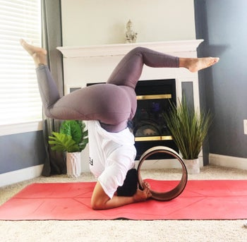 reviewer in headstand position with a brown yoga wheel