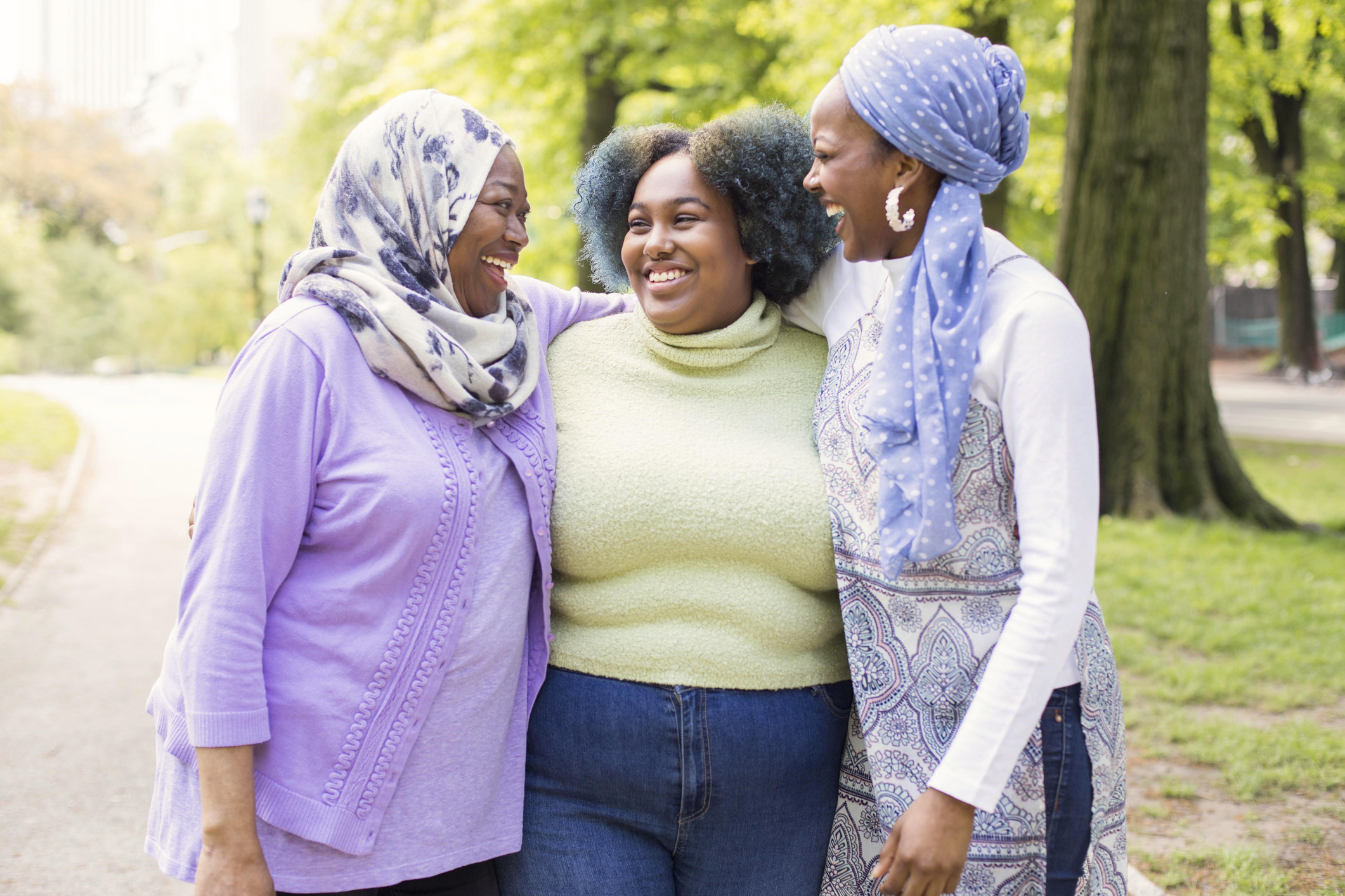 Three Muslim woman laughing together at a park