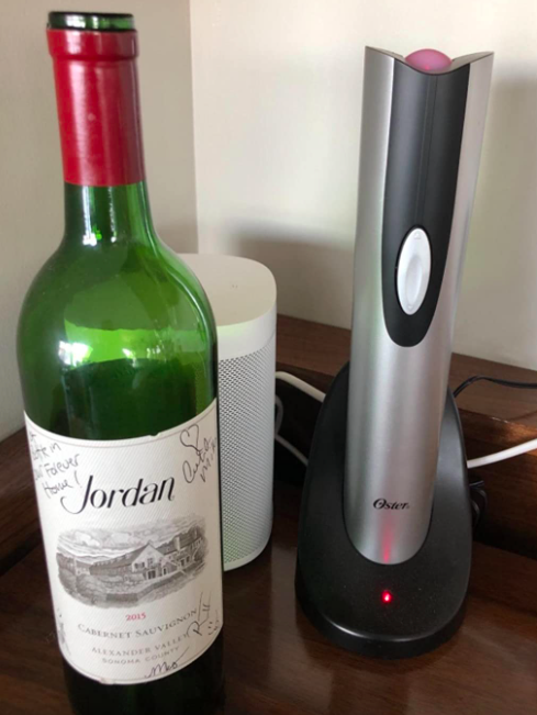 A customer review photo of the wine opener on a counter next to a bottle of wine