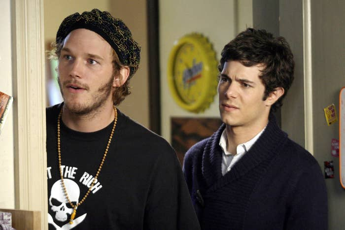 Chris Pratt, in a beanie and skull-and-bones t-shirt, stands next to Brody who's wearing an ascot and a collered shirt