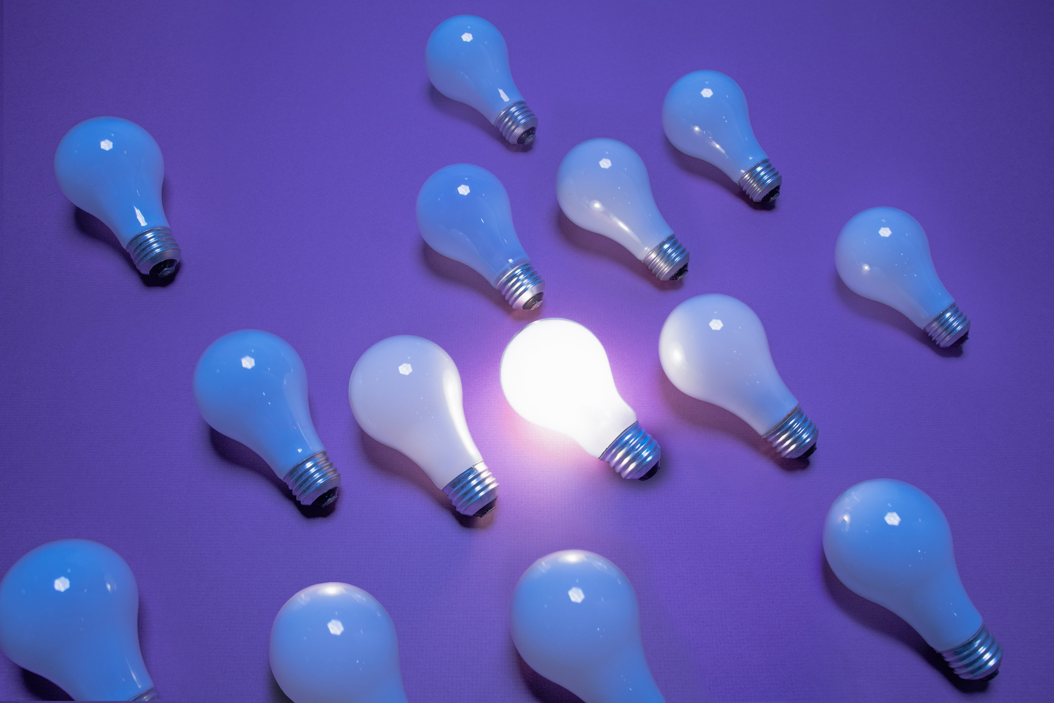 A group of lightbulbs laid out with one on and the others off