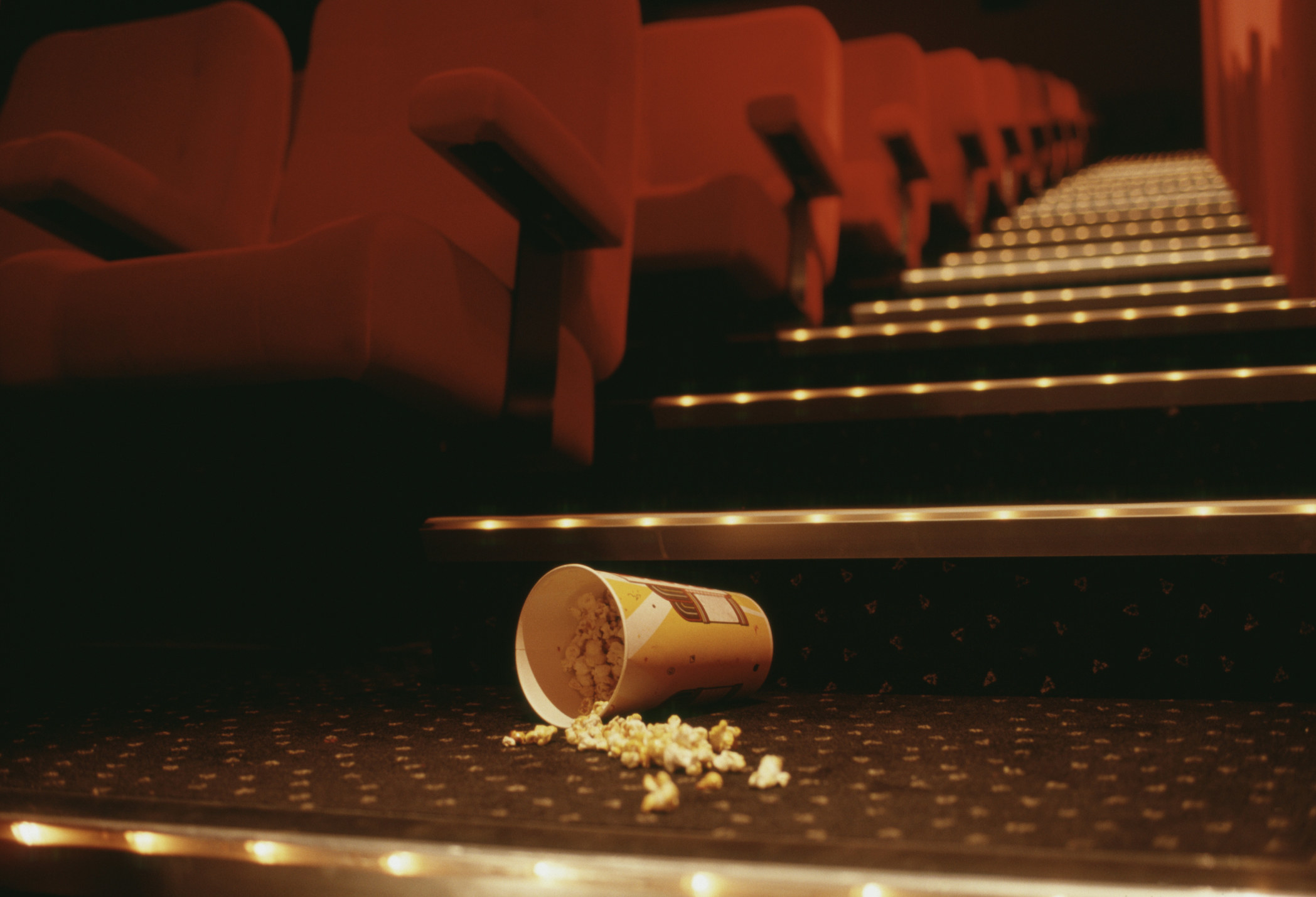 Spilled popcorn at the base of the lit stairs of a movie theater, looking up the aisle with seats on either side