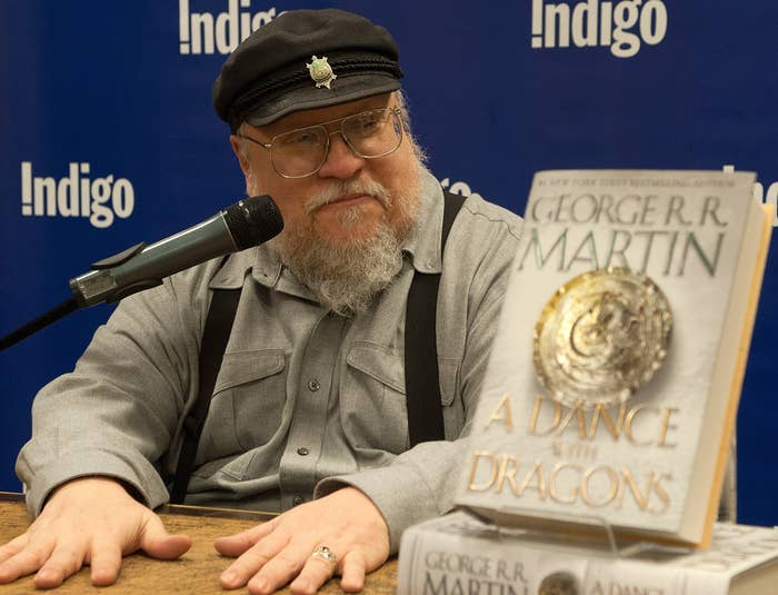 George sits next to a copy of A Dance With Dragons at a book signing