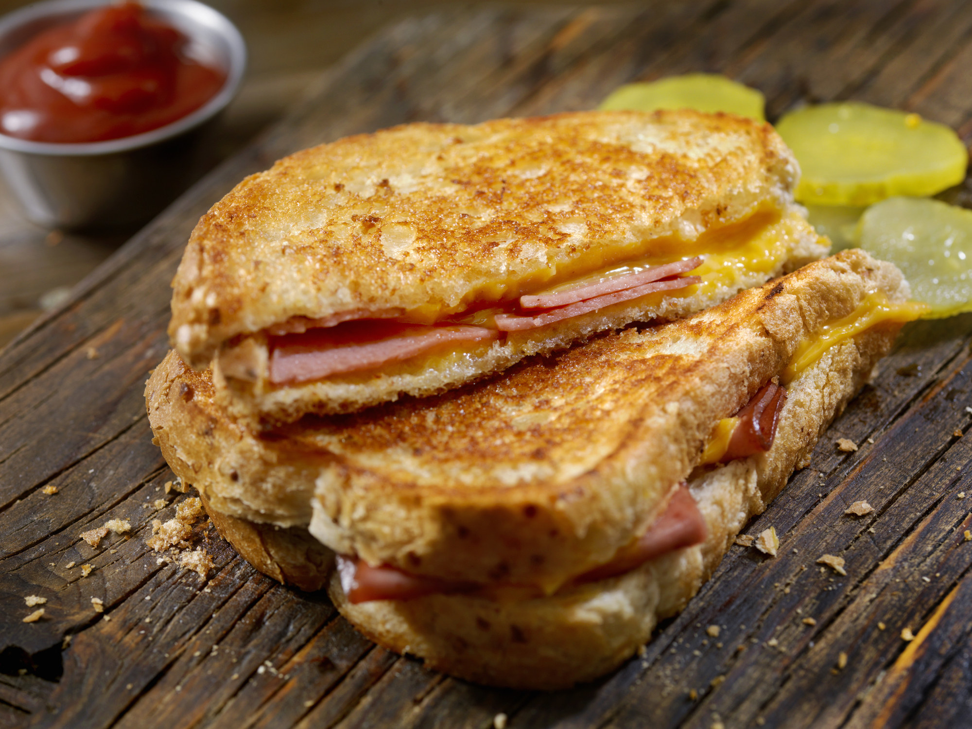 Grilled cheese and bologna sandwich on a wooden board with pickle slices and a metal ramekin of ketchup in the background