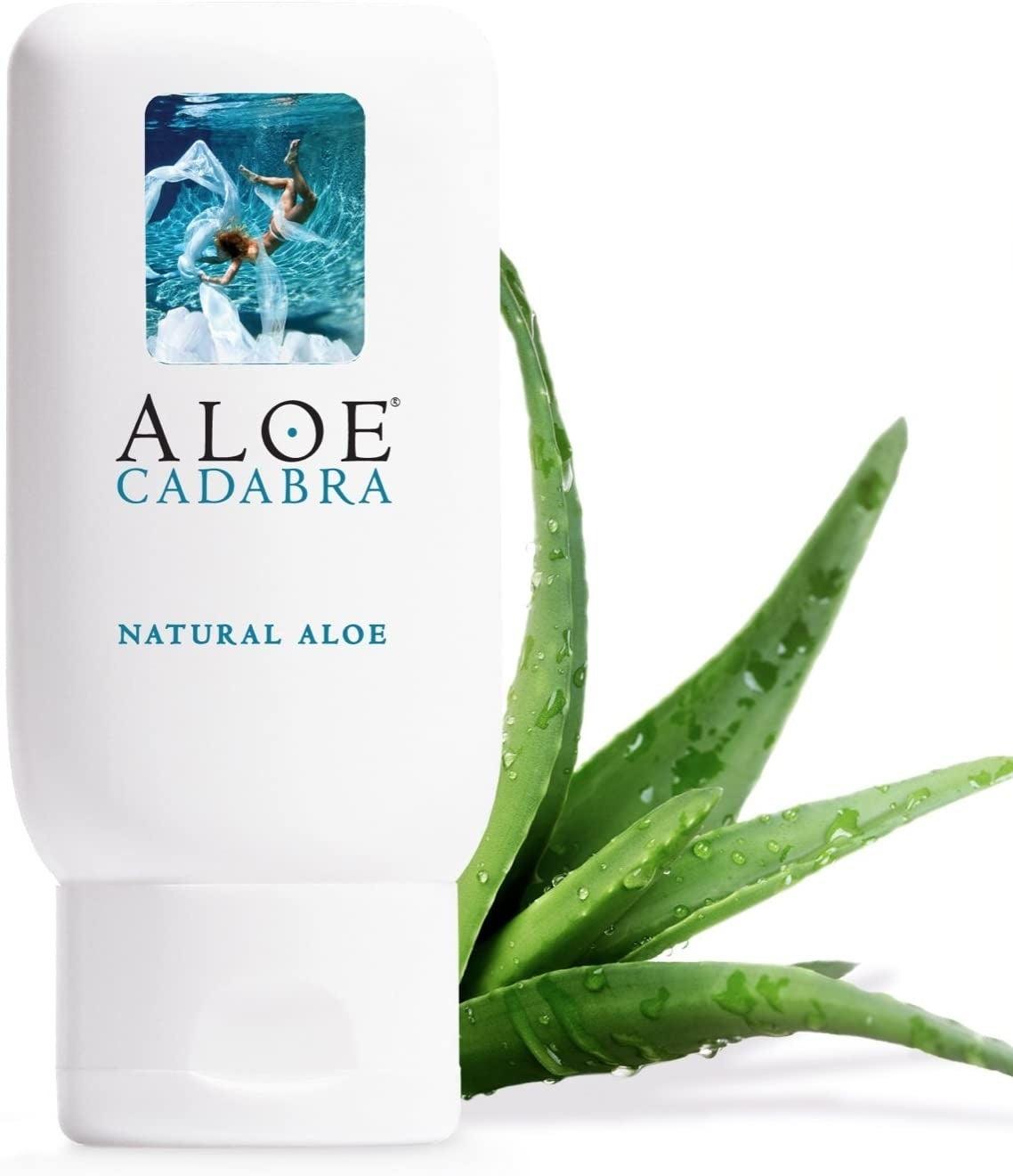 Bottle of Aloe Cadabra lubricant next to aloe plant