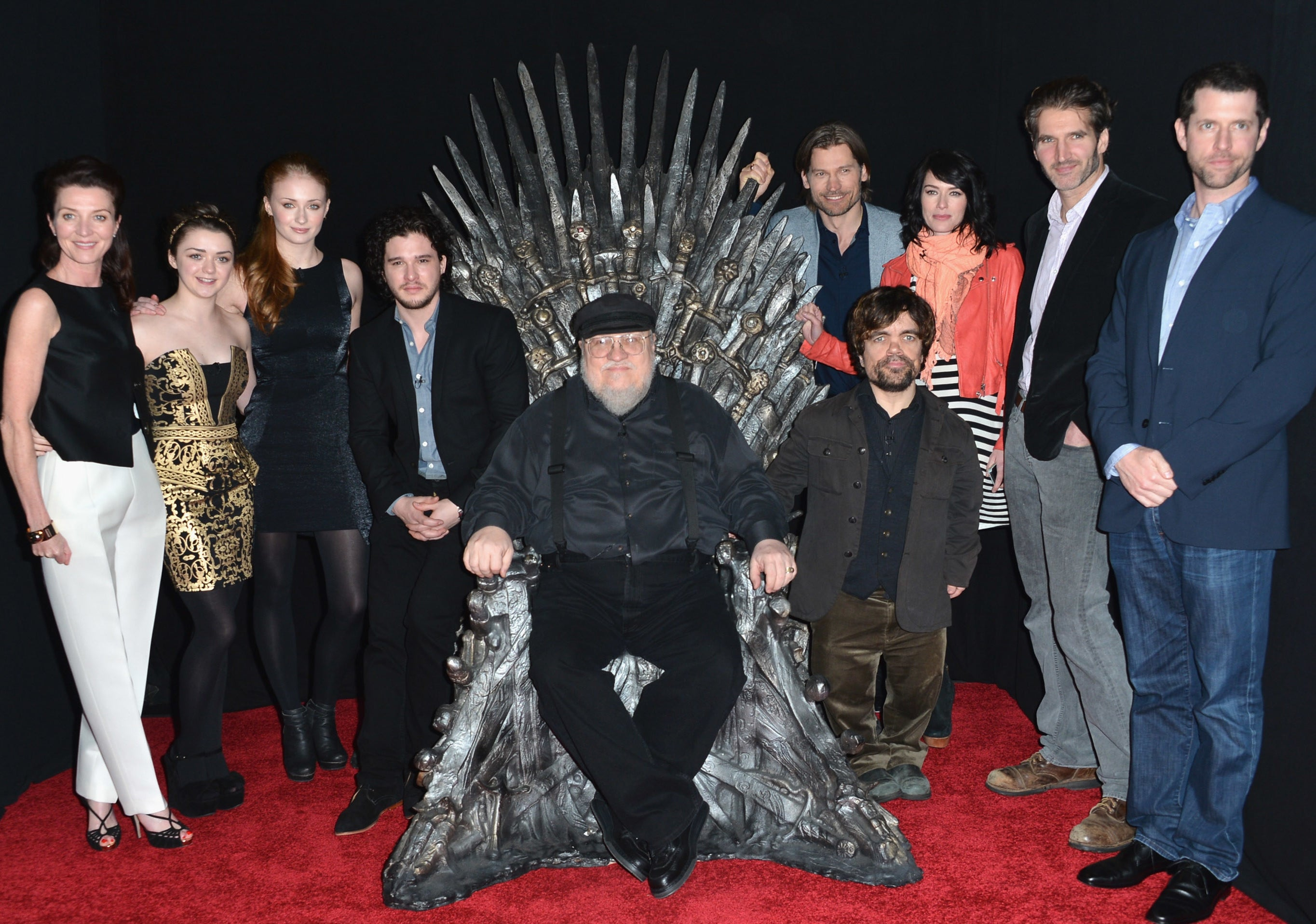 George sits on the throne while surrounded by the show's cast