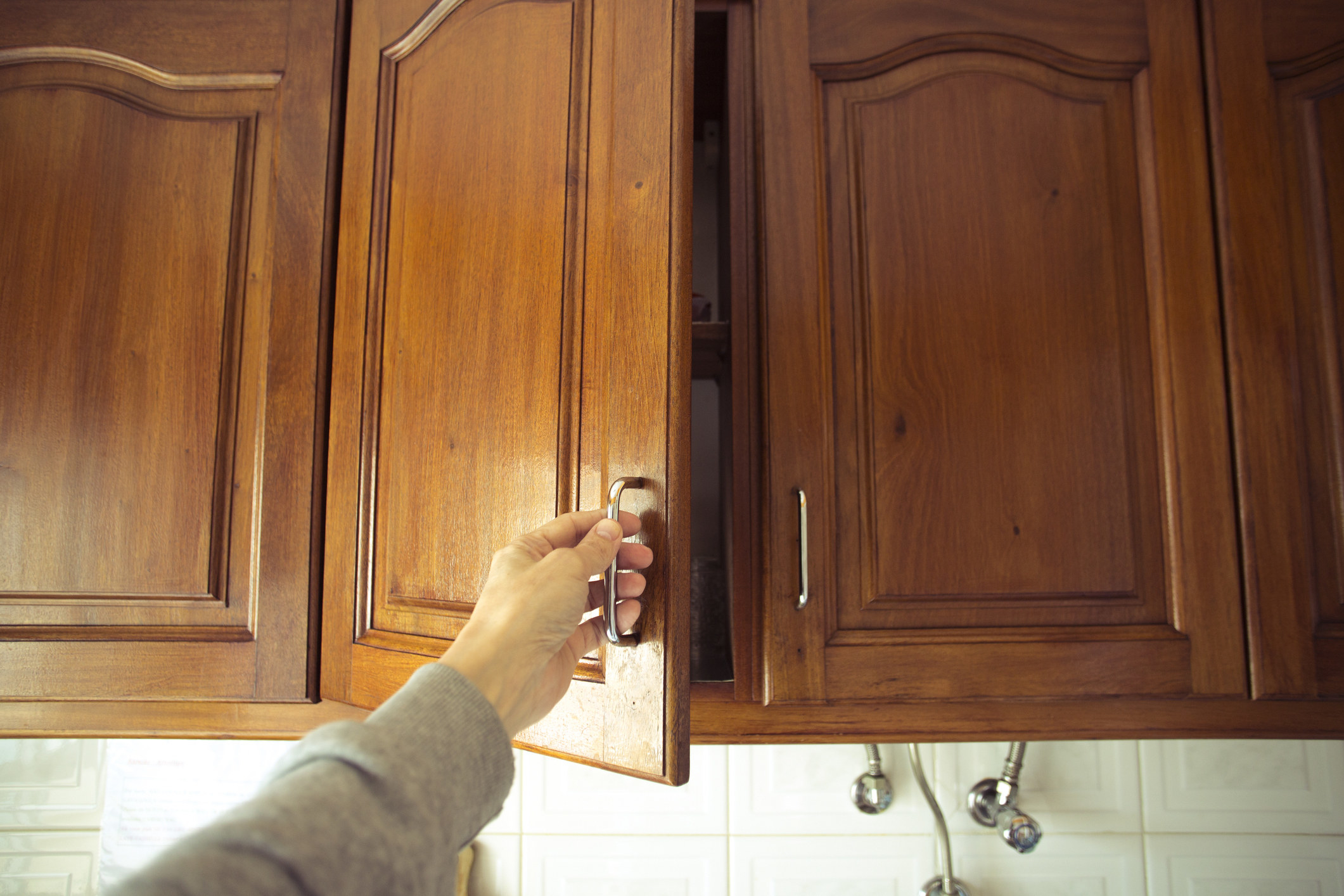 A hand opening an upper cabinet door